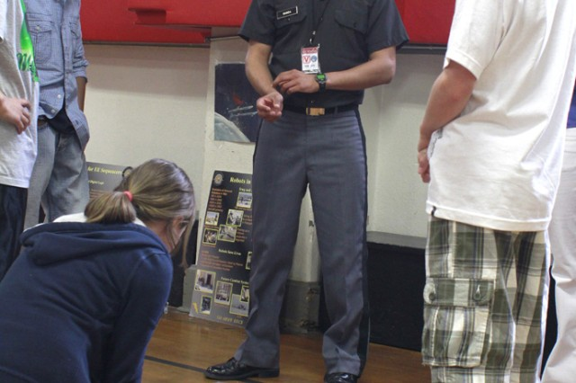 Cadet Agustin Bonda, class of 2011, demonstrates a couple of miniature wheeled-robotics to a group of West Point Middle School students during a visit to the school by the Electrical Engineering and Computer Science Department April 21. The purpose of the trip was to show how the application of math and science was used in creating robotics.