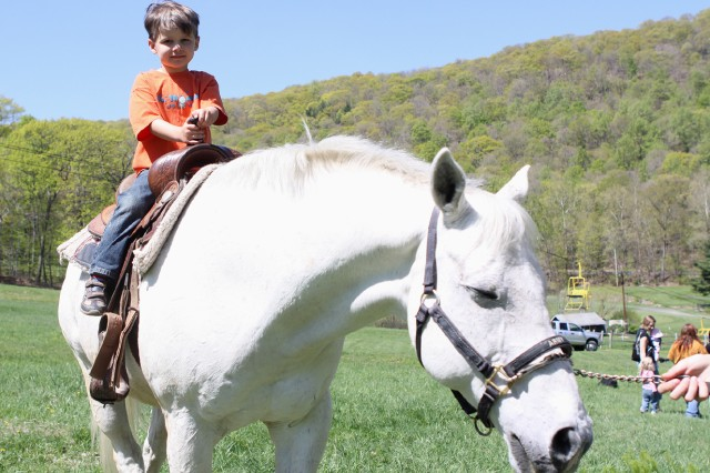 Five-year-old Owen Fetherston takes a ride on Ulysses Grant, a horse from Morgan Farm, during the Month of the Military Child Luncheon April 24 at the Victor Constant Ski Lodge.