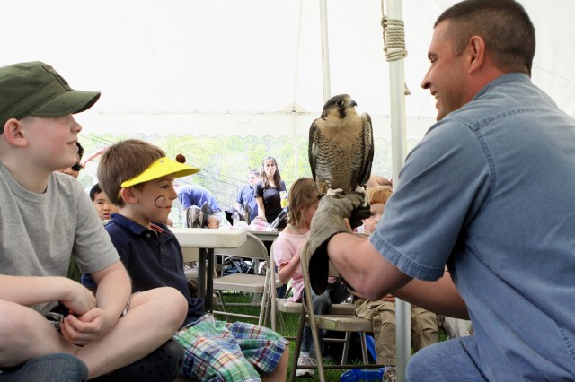 Eight-year-old Sam Gwinn (left) and 5-year-old Luke Bennett look at the Peregrine falcon, which is being held by Brian Robinson, who offers educational wildlife programs.