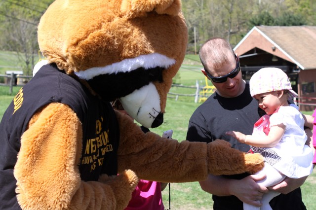 Two-year-old Dreanna White (right), held by dad Staff Sgt. John White, gives five to Ready Raccoon at the MOMC event.