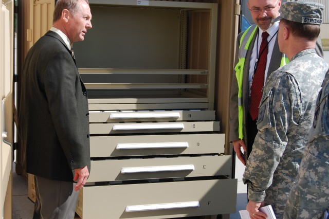 Paul Turner, (left) ASLAC S-3 (Operations), and Kent Selby, Honeywell program manager, brief  how ASL (authorized stockage list) and PLL (prescribed load list) is loaded on APS-3 as Lt. Gen. Mitchell H. Stevenson, the Army's deputy chief of staff for logistics, listens.