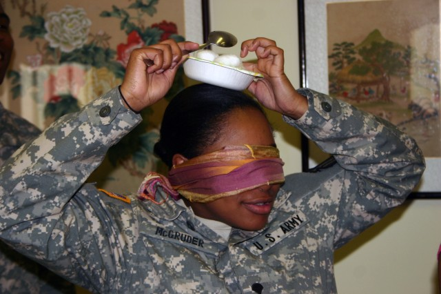 Spc. Natasha McGruder attempts to deposit cotton balls she scooped from a bowl on the table into another container atop her head during a game at Camp Stanley's Pear Blossom Cottage April 30.