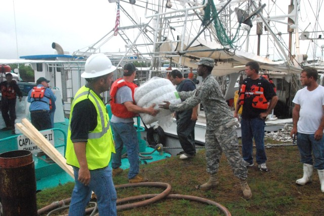 Louisiana National Guard Soldiers help Oil Mop employees load oil booms onto boats at the Breton Sound Marina in Hopedale, La., May 3, 2010.