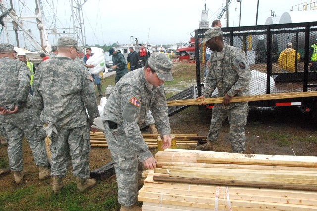 Louisiana National Guard Soldiers load oil booms and wooden stakes onto boats at the Breton Sound Marina in Hopedale, La., May 3, 2010.