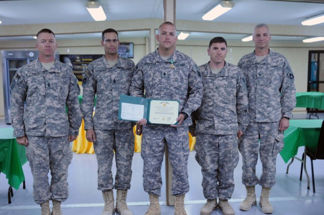 CAMP ARIFJAN, Kuwait - The Command Team of the 53rd Infantry Brigade Combat Team presents Spc. James Odonohugh from the 511th Engineer Dive team an Army Commendation Medal and Certificate for winning the Soldier of the Year Board held here April 30. (Photo by Army Spc. Karen L. Kozub)