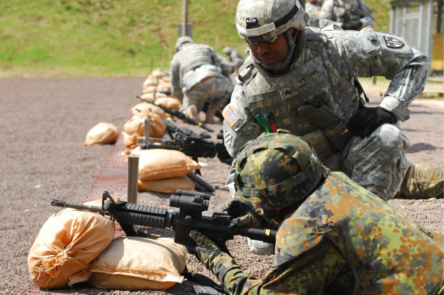 Sgt. Sherman Williams, a motor sergeant with the Headquarters and Headquarters Company, 18th Military Police Brigade, and a St. Louis, Mo., native, assists a German MP from 2nd Company, Feldjäger Battalion 251, at an M4 and M9 range the brigade hosted as a chance for German soldiers to earn their American marksmanship badges.