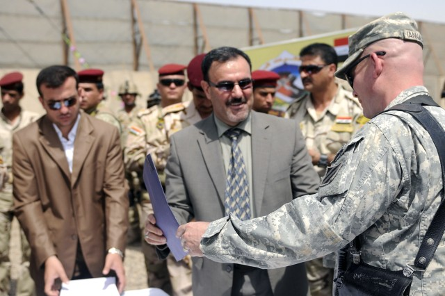 BAGHDAD - Captain Timothy Iannacone (right), the commander of Company B, 3rd Battalion, 69th Armor Regiment, 3rd Infantry Division, hands the final paperwork to Sameer Al-Haddad (left), Secretariat of Receivership for the Government of lraq April 30, transferring control of Joint Security Station Ur from the U.S. to Iraqi Security Forces. Iannacone said he was impressed with the Iraqi Army unit's proficiency and that they have shown they are prepared to take over security of the surrounding area. (U.S. Army photo by Pvt. Emily Knitter, 1 AAB, 3ID PAO, USD-C)
