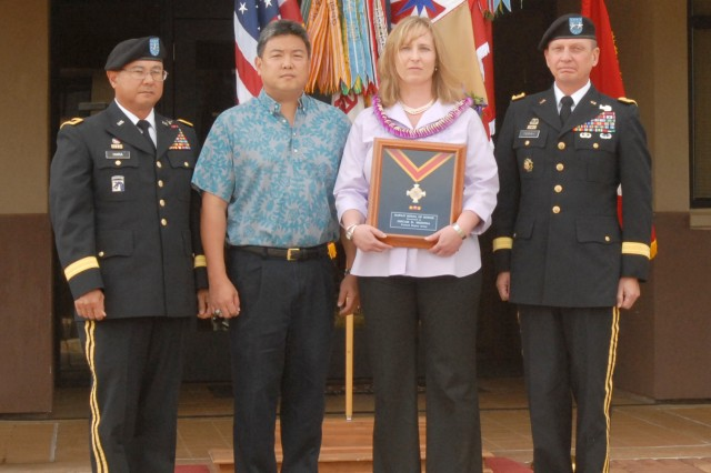 Mrs. Beate Medina accepts the Hawaii Medal of Honor on behalf of her late husband, Staff Sgt. Oscar D. Medina during a ceremony Apr. 30.  Also pictured from left: Brig. Gen. Gary Hara, Assistant Adjutant General, Hawaii Army National Guard; Hawaii State Representative Mark Takai; and Maj. Gen. Michael J. Terry, commanding general, 8th Theater Sustainment Command.