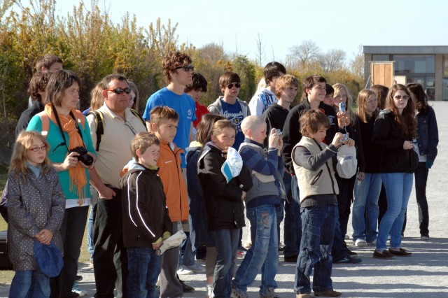 The crowd waits patiently to have their picture taken with the 7th Civil Support Command Color Guard. Each person could hardly contain their emotion and gratitude on their faces. The color guard was present to pay tribute to the 90th Infantry Division's wartime efforts and sacrifices during World War II, honoring their colors during the battle streamer ceremony.