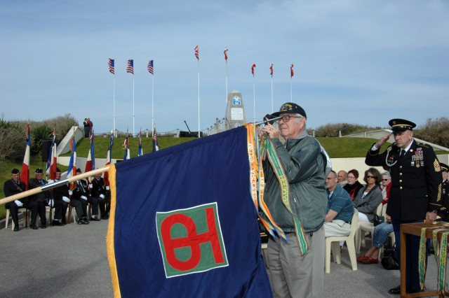 Retired Sergeant 1st Class John Roman, a native of Fenwick Island, Del., places the Northern France battle streamer on the 90th Infantry Division colors at a battle streamer ceremony on Utah Beach April 27. This was one of four commemoration ceremonies the U.S. Army Reserve ambassadors of the state of Texas held in honor of the 65th Anniversary of V-E Day during their visit to Europe.