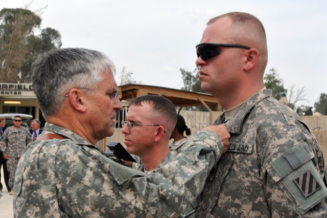 Sergeant John Z. Snell, 1/64 Armor, 2nd HBCT, 3rd ID, is presented the Bronze Star with Valor by Army Chief of Staff Gen. George W. Casey, Jr., during a ceremony at Contingency Operating Site Diamondback, April 27.