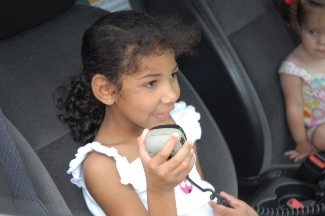 Breanna Lofton, 7, speaks through a police car public announcement system at Fort Jackson's annual Bike Rodeo last week.