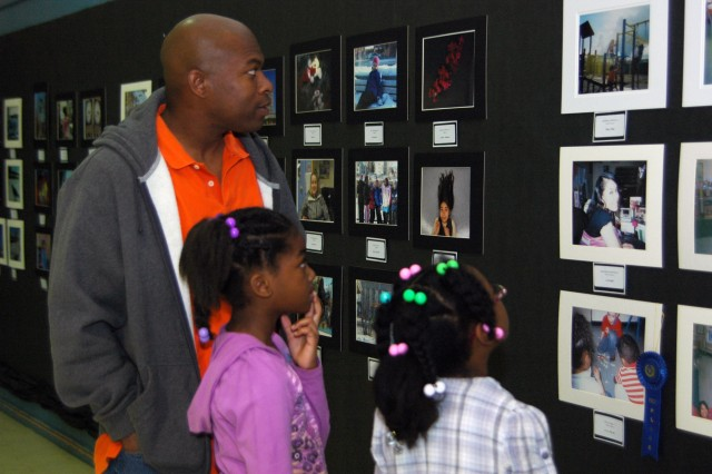 """FORT WAINWRIGHT, Alaska - Sgt. 1st Class Michael Richardson, A Company, 1st Battalion, 52nd Aviation Regiment, 16th Combat Aviation Brigade, and his daughters Iyana, 9, and Makayla (right), 8, look at photos in the Child, Youth and School Services School Age Services photography exhibit. One of Iyana's photos won first prize for her age group in color processing. Twenty-four children from SAS, ranging in age from 6 to 11, participated in the first annual 4-H and Boys and Girls Clubs of America photography contest which challenged them to utilize various light sources, subjects and types of processing including digital, color and black and white film throughout the 10-week photography class. """"They were able to learn that everything looks so different when you're looking through a camera,"""" said Jonny Cain, CYSS Homework Lab instructor and one of the teachers of the photography class. """"I would like for them to always look at everything differently because of that."""" Six winners were chosen; one from each age group and type of processing. Winners' photos will compete at the regional competition and if successful there, will go to the national competition, Cain said."""