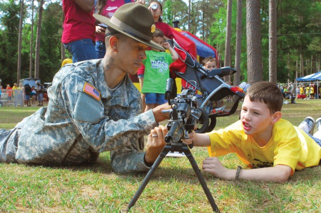 SGT Brandon Morris shows 10-year-old Logan Hobson, a fourth-grader at McBride Elementary School, how to how to operate an M249 April 30 during the school's annual field day.  Activities included fair rides, military displays and relay races, and carnival-style snacks were available for purchase.