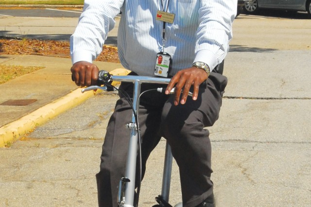 Charles Marshall, resource efficiency manager with the Directorate of Public Works' Environmental Management Division, uses a folding bike, which collapses into a two-foot square in about 90 seconds, to commute to places on post from his office in Meloy Hall.