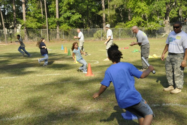 Sergeant Phillip Phinesee, Spc. Frankie Nugent and Spc. Christopher Aker cheer on the students of Brittin Elementary at Fort Stewart in a relay race during the school Field day, April 29.
