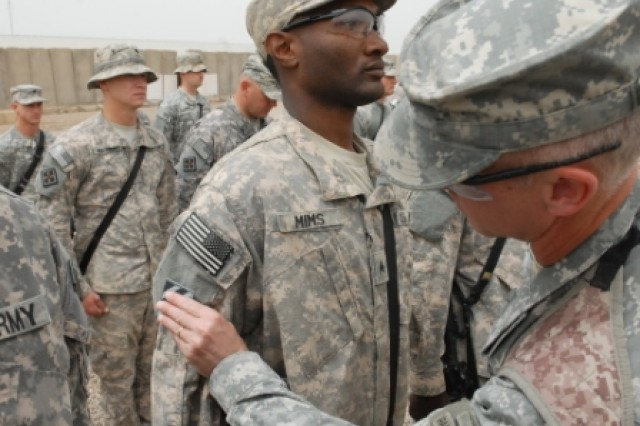 During a formation in front of the headquarters of 3rd Heavy Brigade Combat Team, 3rd Infantry Division, at Contingency Operating Site Kalsu, Iraq, Sgt. Jamie Mims, an engineer assigned to the 858th Engineer Company, stands at attention as Col. Pete Jones, the commander of the 3rd HBCT, places a 3rd Infantry Division combat patch on his arm, April 22, 2010. The 858th Engineer Company cleared, shaped and compacted over 60 acres during their time at COS Kalsu.