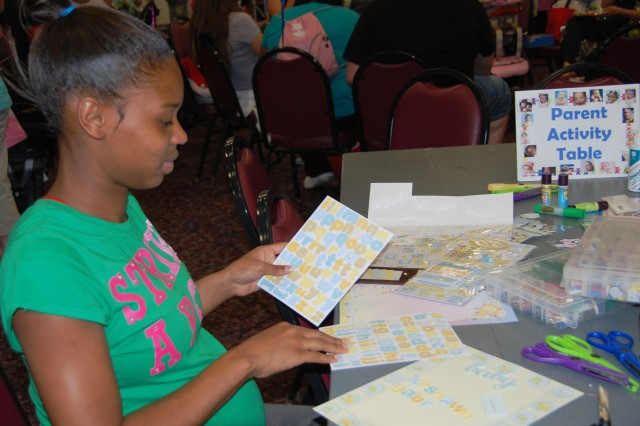Desiree Hillman enjoys creating a page for her baby's scrapbook during Operation Baby Shower April 30 at Fort Sam Houston.