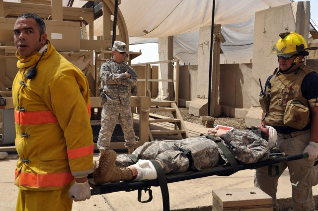 BAGHDAD - Firefighters evacuate a simulated casualty during a mass casualty exercise held May 3 at Camp Liberty. The purpose of the exercise was to certify that personnel in a combat environment are able to effectively respond to a mass casualty event. (U.S. Army photo by Spc. Kim Wilkins, 1AD, USD-C)