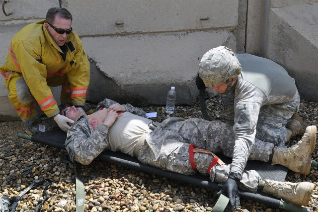 BAGHDAD - A firefighter with Camp Liberty's emergency medical services and a medic with 1st Armored Division's battalion aid station work together to place a simulated casualty onto a litter carrier during a mass casualty exercise May 3 at Camp Liberty. (U.S. Army photo by Spc. Kim Wilkins, 1AD, USD-C)