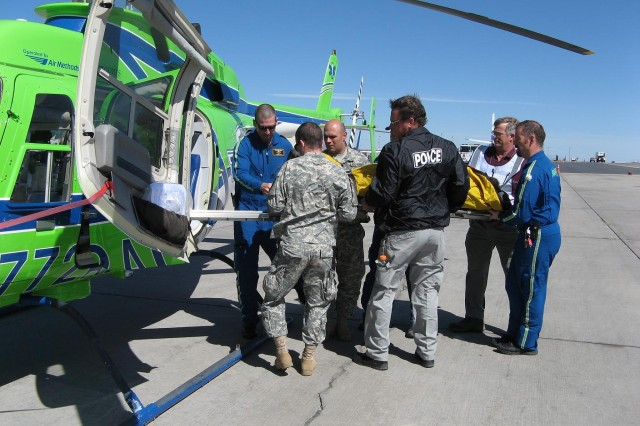 """DENVER---The """"Mountain Move"""" exercise was truly a joint venture as representatives from several agencies worked to load a patient onto an AirLife of Denver medical evacuation helicopter.  Patients were transported from the reception area by ground and air ambulances to local hospitals."""