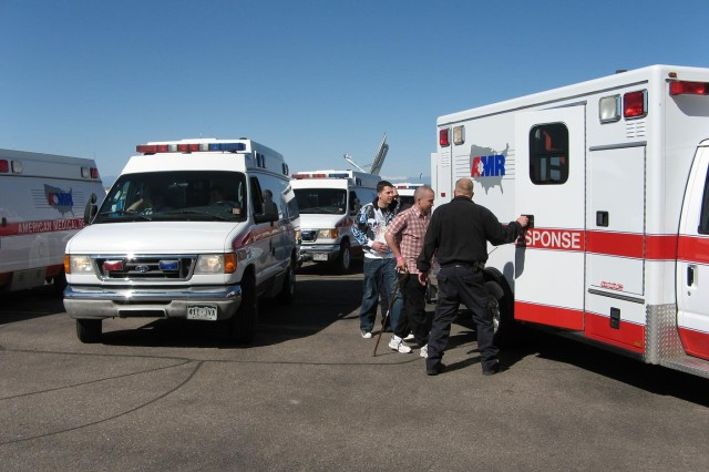 DENVER---A transportation and distribution supervisor assists an ambulance crew as they prepare to transfer a patient from a rickshaw onto a gurney for transport to a local Denver hospital.  Ambulance crews kept track of their patients and hospital delivery locations.