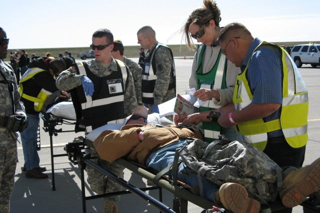 DENVER---Medical professionals from various agencies checked the off-loaded patients' conditions and status before they were moved inside the hangar that served as a reception, triage and treatment area.