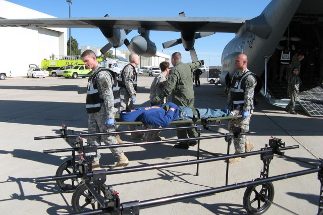 """DENVER---Fort Carson medical Soldiers off loaded the patients from the WYANG C-130 and transferred them to wheeled """"rickshaws"""" before transporting them to the Signature Aviation hangar that served as a reception, triage and treatment area."""