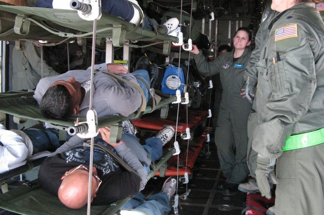 DENVER---Warrior Transition Battalion Soldiers lie in racks of transport litters inside a Wyoming Air National Guard C-130 aircraft while receiving instructions from the plane's crew.  The Soldiers portrayed injured civilians who were notionally transported from Utah.