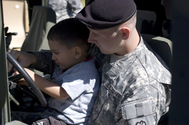 SCHOFIELD BARRACKS, Hawaii - Spc. William Johnson helps Aiden Ramey explore driver's seat options, including starting the vehicles, honking the horn, flipping switches and turning on blinkers and fans. As part of Month of the Military Child, Soldiers from Company D, 2nd Battalion, 35th Infantry Regiment, 3rd Brigade Combat Team, 25th Infantry Division, visited the Child Development Center to allow children an up-close and hands-on view of Army equipment like trucks, gas masks and radios.