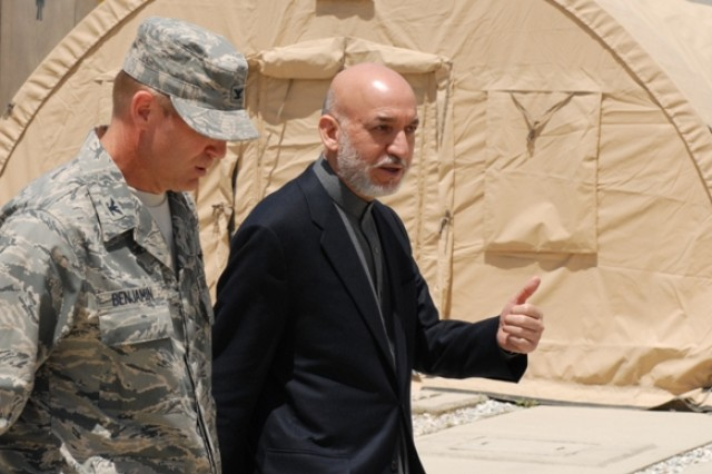 BAGRAM AIRFIELD, Afghanistan - Afghanistan President Hamid Karzai takes to U.S. Air Force Col. Christian Benjamin, Task Force Medical commander, as they walk into the Staff Sgt. Heathe Craig Joint Theater Hospital at Bagram Airfield, during a surprise visit by Karzai, May 8. Karzai met with wounded Afghan National Army and U.S. servicemembers during the visit. The visit coincides with a trip to Washington D.C. next week to meet with his counterpart, U.S. President Barak Obama among other to discuss the current and future plans for Afghanistan.  (Photo by Spc. Jay Venturini, 304th Public Affairs Detachment)