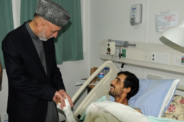 BAGRAM AIRFIELD, Afghanistan - Afghanistan President Hamid Karzai visits with Omar Mohammad, a Soldier in the Afghan National Army, assigned to the 6th Kandak, 3rd Brigade, 203rd ANA Corps, at Staff Sgt. Heathe N. Craig Joint Theatre Hospital, Bagram Airfield, Afghanistan, May 8.  Omar was wounded by and improvised explosive device April 17, Karzai visited several wounded Servicemembers and spoke with ANA troops and coalition forces during his visit to Bagram Airfield. (Photo by U.S. Army Spc. Charles J. Thompson, CJTF-82 Public Affairs)