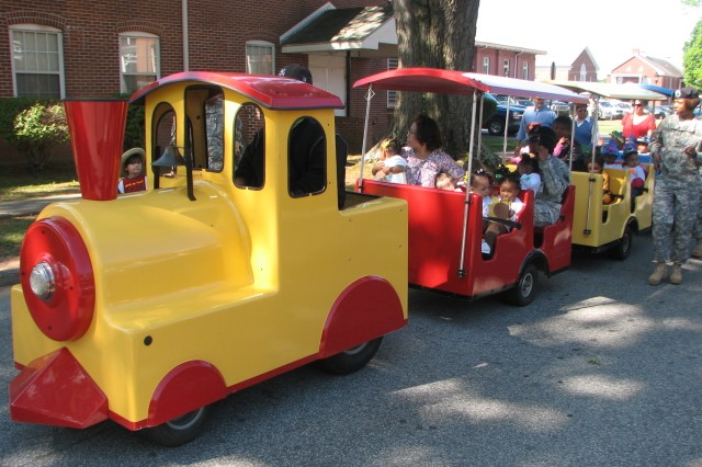 """Children from the Child Development Center take a ride with their teachers and servicemembers in a toy train during the Child's Day Parade at Fort McPherson April 28. The parade, themed """"Discover Science,"""" closed out the Army's """"Month of the Military Child."""" The kids were cheered on by servicemembers and Civilian employees as they travelled the post."""