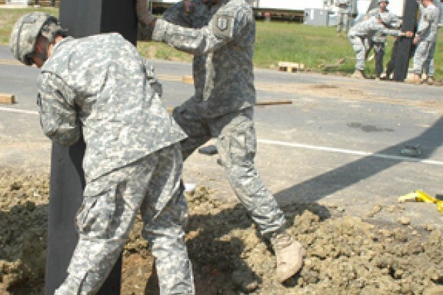 "Left: Pvt. Levi Oneal (left) and Spc. Kenneth Kelso, 814th MRBC guide a ""Tigerland"" arch into place for the 162nd Infantry Brigade on North Fort Polk April 21."