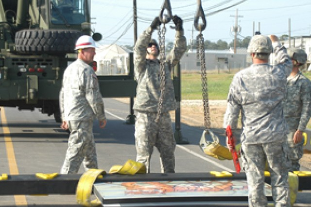 "Above: Pvt. Levi Oneal (center), 814th Multirole Bridge Company, 1st Maneuver Enhancement Brigade, hooks chains to a ""Tigerland"" arch while preparing to emplace it for the 162nd Infantry Brigade on North Fort Polk April 21 as Sgt. 1st Class Jeffrey Hammack, 162nd (left), supervises."