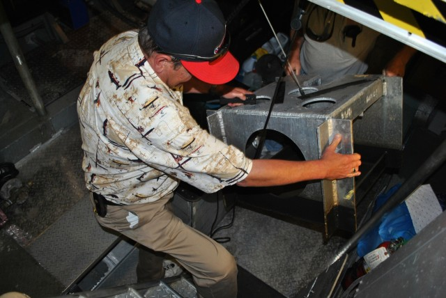 Tony Maze pulls a mutlibeam device used for surveying out of the water.jpg