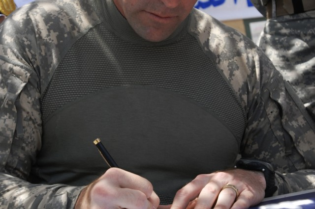 JOINT SECURITY STATION SHEIKH AMIR, Iraq - Lt. Col. Mike Lawrence, commander, 2nd Battalion, 23rd Infantry Regiment, 4th Stryker Brigade Combat Team, 2nd Infantry Division, signs a document May 7 stating the JSS would no longer be run by U.S. Soldiers, and would now be under the control of the Iraqi Army. Soldiers with Company A, 2nd Bn., 23rd Inf. Regt., 4th Stryker Brigade Combat Team, 2nd Infantry Division, lived on the JSS with their Iraqi partners since Jan. 9 and withdrew from the base as a part of the U.S. military's responsible drawdown of forces in Iraq. (U.S. Army photo by Pfc. Kimberly Hackbarth, 4th SBCT PAO, 2nd Inf. Div., USD-C)