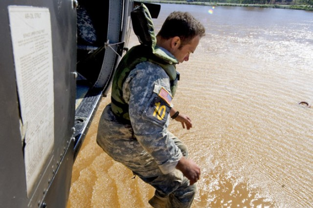 Staff Sgt. Thomas West, 6th Ranger Training Battalion, jumps from a Blackhawk into a lake where they then drag their poncho raft and gear to the shore during the grueling three-day Best Ranger competition at Fort Benning, Ga.