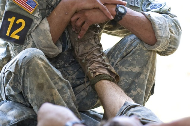 Staff Sgt. Bernado Mota, a Ranger with the 82nd Airborne Division, helps teammate Staff Sgt. Jeremiah Waggoner stretch out severe cramps during the grueling three-day Best Ranger competition at Fort Benning, Ga.