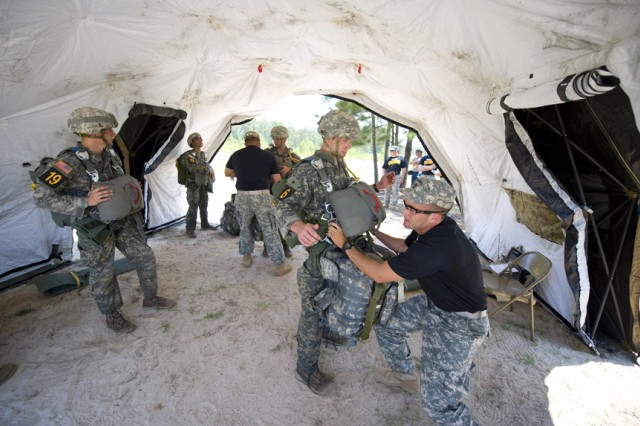 Teams get securely fastened to their parachutes prior to conducting a spot jump during the 2010 Best Ranger competition. Teams were scored depending how close they landed to the designated marks.