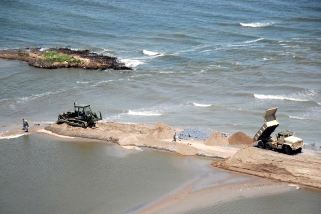 Heavy equipment operators from the Louisiana National Guard bulldoze sand to close a strait between two peninsulas near Grand Isle, La., May 10, 2010. The closure will be a secondary defense in addition to the boom line in the Gulf of Mexico to prevent an oil spill from reaching further inland.
