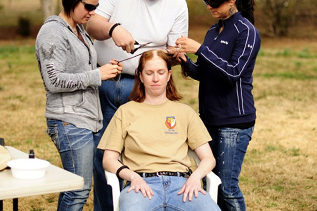 """Chaplain (Capt.) Melissa Hale's friends and family braid her hair before shaving it off so that they may keep the braids. Hale and her husband threw a hair-shaving """"party,"""" knowing that her trademark red hair would fall out as a result of"""