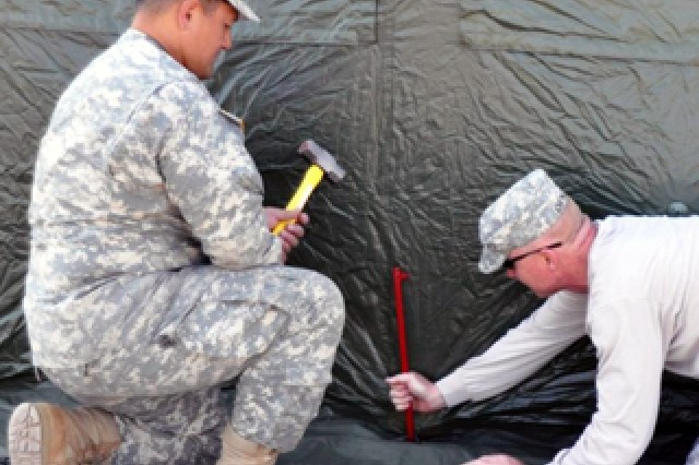 Majors Lloyd Togisala (left) and Kevin Emerick set up the shelter that was used as the headquarters for the 405th Army Field Support Brigade's forward command post during the brigade's recently concluded deployment to Grafenwoehr, Germany, in support of the Austere Challenge '10 exercise.