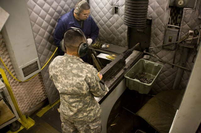 Spec. Jose Lopez Herdandez with 2nd Brigade Combat Team, 1st Cavalry Division, fires a .50-caliber machine gun in Anniston Army Depot's Small Arms Repair Facility.