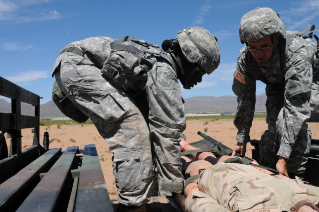 FORT BLISS, Texas - Bronx, New York native 1st Lt. Marsha McLean, C Company, 125th Brigade Support Battalion, 3rd Brigade Combat Team, 1st Armored Division, receives help loading a dummy onto the rear of a truck during a combat testing lane of the Expert Field Medical Badge Testing held April 27 to May 7. The lanes involved successfully loading four dummy onto the truck within 15 minutes. McLean completed the course and earned a badge that only 2 percent of officers Army-wide is currently eligible to wear.  (U.S. Army photo by Sgt. Roger RyDell Daniels, 16th Mobile Public Affairs Detachment)