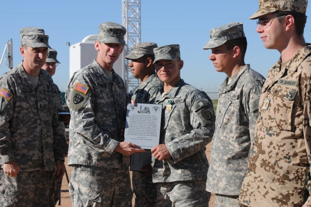 """FORT BLISS, Texas -- Fort Bliss Commanding General, Maj. Gen. Howard B. Bromberg, presents Staff Sgt. David Smith, U. S. Army Dental Command, with an Expert Field Medical Badge; the Cpl. Thomas J. Kelly Award; an Army Commendation Medal, an EFMB coin of excellence for the least amount of """"NO GOs"""" and for the best land navigation skills; and the """"Feet of Flight Award"""" for the fastest road march time Friday, May 7, during the EFMB test graduation. Smith finished the 12-mile road march in 2 hours, 31 seconds. Sgt. Gilberto Roman, A Co. William Beaumont Army Medical Center, and German Army Major, Dr. Walter Barclay, wait to receive their EFMB. Command Sgt. Maj. David Davenport, Fort Bliss command sergeant major, looks on. (U.S. Army photo by Sgt. Roger RyDell Daniels, 16th Mobile Public Affairs Detachment)"""