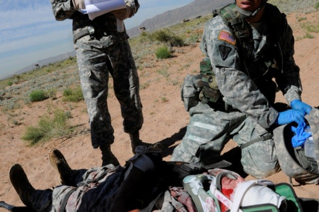 FORT BLISS, Texas -- Staff Sgt. Addiel Flores, an operating room specialist with William Beaumont Army Medical Center, performs first aid on mock casualty Sgt. Kurtis Rose of Company A, 501st Brigade Support Battalion, 1st Brigade Combat Team, 1st Armored Division, May 5. Flores practiced treating casualties of a helicopter crash simulation during the Expert Field Medical Badge test held April 27 to May 7. (U.S. Army photo by Sgt. Richard Andrade, 16th Mobile Public Affairs Detachment)