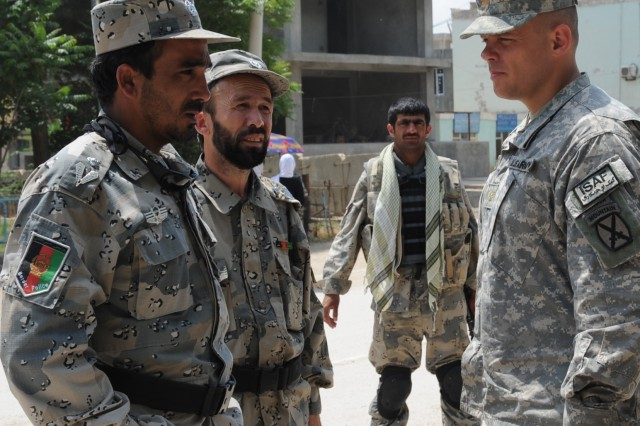 Maj. Cloyd Smith, right, operations officer, Headquarters and Headquarters Company, 1st Brigade Special Troops Battalion, meets with Maj. Ismatula, left, commander, Quick Response Force Company, 3rd Kandak, Afghanistan National Border Patrol, and Maj. Hamidala, supply officer for 3rd Kandak, ANBP, as an ANBP member looks on. They met May 6 to discuss proposed sites for the building of the joint combat outpost in Heyratan, Afghanistan.