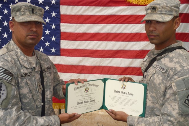 First Lt. Gilbert Alvelo Jr., left, congratulates his younger brother, Sgt. Christopher Alvelo, on re-enlisting for six more years in the Army. The elder Alvelo had the honor of administering the oath of re-enlistment.