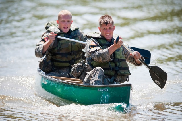 """Capt. Derrick Anderson (front) and Staff Sgt. Chris Malone, the two-man team representing """"The Old Guard"""" maneuver a canoe through the water on day three of the David E. Grange Jr. Best Ranger Competition held May 7-9, at Fort Benning, GA. This event was one of several that Ranger teams must complete in order to continue on into the competition."""